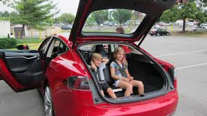 Family car 7 Tesla Model S Red doors open and two children sitting in rear seats